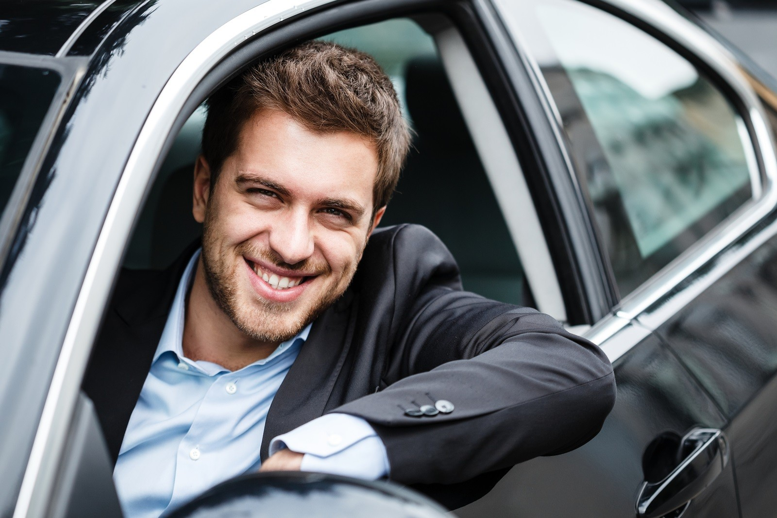Portrait of an handsome guy driving his car